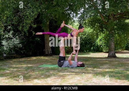 Giovane uomo a praticare yoga in giardino, giacente sul retro donna di bilanciamento su piedi Foto Stock