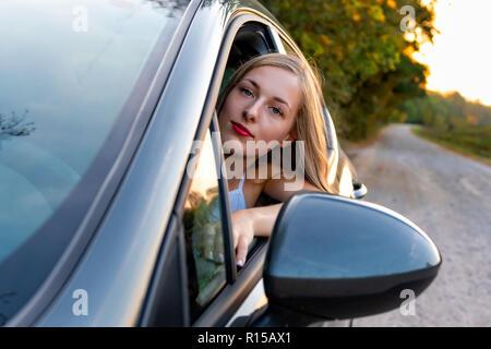 Una giovane e bella donna con capelli lunghi si siede al volante della vettura e guarda fuori dalla finestra. Foto Stock