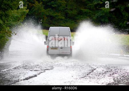 La guida di veicoli attraverso strade allagate in Bowness, Lake District UK Foto Stock