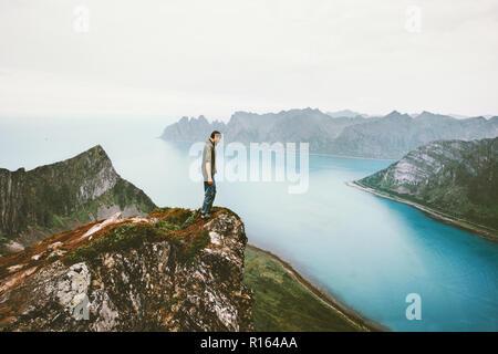 L'uomo traveler in piedi da sola sulla scogliera di montagna sopra bordo fjord avventura marittima lifestyle vacanze outdoor in Norvegia la solitudine delle emozioni Foto Stock