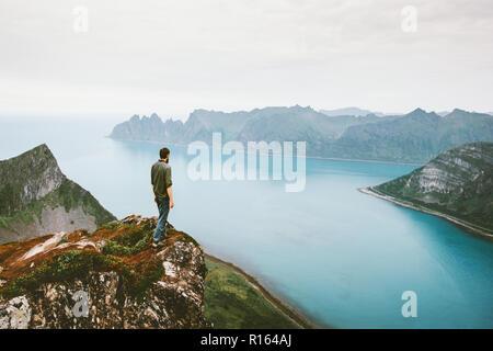 Uomo attivo in viaggio a piedi da sola sulla scogliera di montagna sopra bordo avventura marittima uno stile di vita sano vacanze estive all'aperto in Norvegia la solitudine delle emozioni Foto Stock