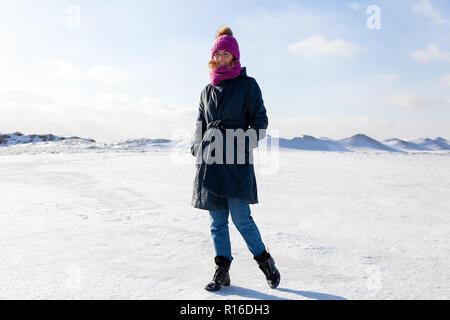 Una giovane donna in una maglia rosa hat, mantello nero gode di natura invernale, camminando sul mare ghiacciato al polo nord intorno al cielo blu nel gelido inverno Foto Stock