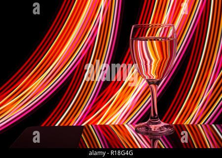Bicchiere da vino / bicchieri su uno sfondo nero con luce al neon di pittura