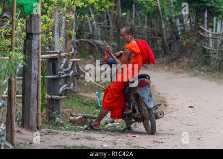 Don Det, Laos - 23 Aprile 2018: il giovane monaco buddista seduto su uno scooter e utilizzando il suo telefono cellulare in un remoto villaggio del sud Laos Foto Stock