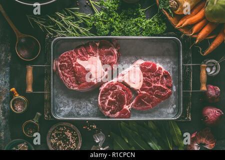 Materie di carni bovine shin con osso per brodo, zuppa o lo stufato nella barra in metallo con ingredienti per una gustosa cucina: ortaggi a radice, erbe aromatiche e spezie su rusti scuro Foto Stock