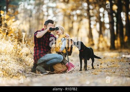 Un maturo padre con un cane e un bambino figlio in una foresta autunnale, utilizzando un binocolo. Foto Stock