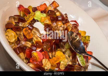 Gummi Cola bottiglie caramelle in una ciotola bianco pronto con un cucchiaio su di esse a una festa per bambini Foto Stock