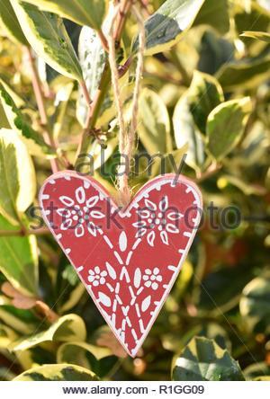 Decorazione per albero di Natale rosso cuore folk con holly Foto Stock
