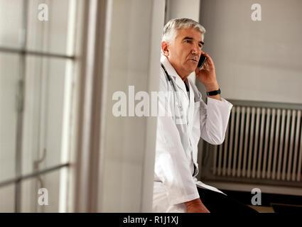 Senior medico maschio si trova in un corridoio a parlare sul suo telefono cellulare. Foto Stock