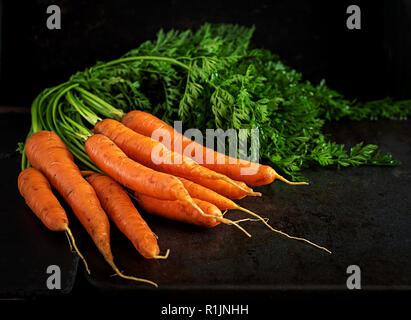 Mazzo di carote fresche con foglie verdi su sfondo scuro. Foto Stock