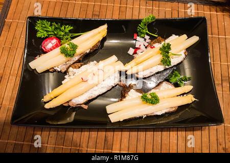 A basso contenuto calorico cibo. Asparagi sul pane nero con Ravanelli e quark fresco Foto Stock