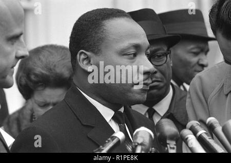 Martin Luther King Jr., testa e spalle ritratto, rivolto verso destra a microfoni, dopo un incontro con il presidente Johnson a discutere dei diritti civili, alla Casa Bianca, 1963 Foto Stock
