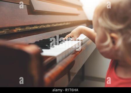Educazione musicale - bambino premendo tasti di pianoforte Foto Stock