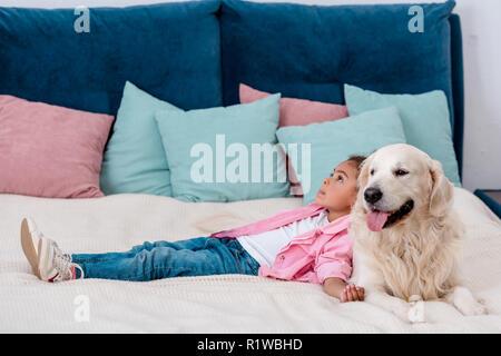 Adorabili poco african american kid in camicia rosa sdraiato sul letto e appoggiandosi a dog Foto Stock
