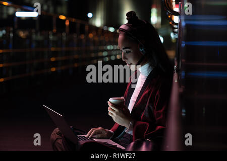 Attraente ragazza asiatica in kimono seduta ed essendo la video chat su strada con luci al neon, città di future concept Foto Stock