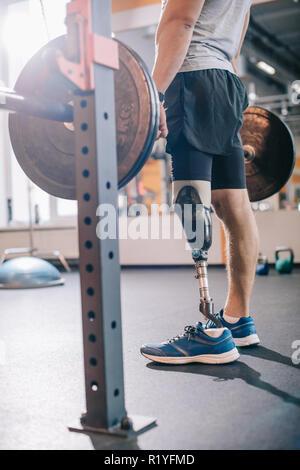 Ritagliato colpo di uomo con gamba artificiale lavora con barbell in palestra