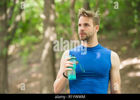 Ad appena un minuto di riposo. Uomo aspetto atletico detiene una bottiglia con acqua. L'uomo atleta nello sport vestiti si preoccupa per il bilancio idrico. Sport e stile di vita sano. Atleta bere acqua dopo la formazione nel parco. Foto Stock