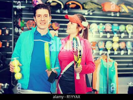 Giovane donna con uomo sono in piedi in sportwear e azienda moderna padel racchette e palle nel negozio di sport Foto Stock