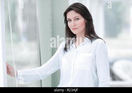 Gli affari seri donna in piedi vicino alla finestra in ufficio.