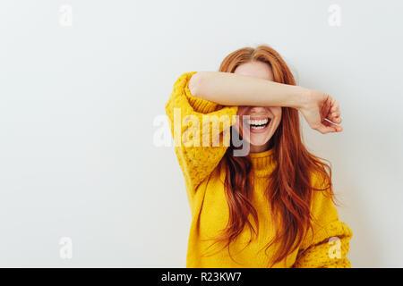 Donna che copre la sua gli occhi con il suo braccio mentre attende una sorpresa Foto Stock