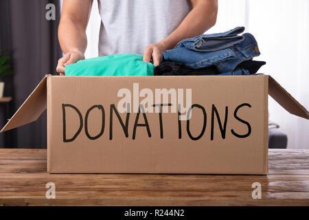 Giovane uomo donando vestiti in donazione Box sulla scrivania in legno