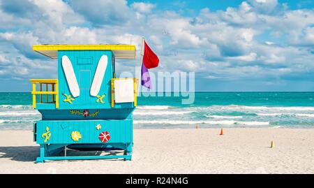 South Beach, Miami, Florida, bagnino casa in un colorato stile Art Deco su nuvoloso cielo blu e Oceano Atlantico in background, famosa in tutto il mondo percorso di viaggio Foto Stock