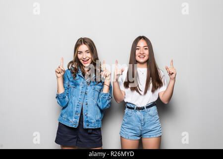 Ritratto di razza mista due ragazze allegro puntando le dita su isolate su uno sfondo grigio Foto Stock