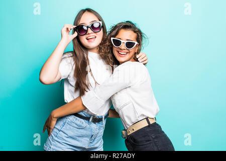 Due belle donne multietnica indossando cappelli di paglia a sorridere guardando la fotocamera su sfondo blu Foto Stock