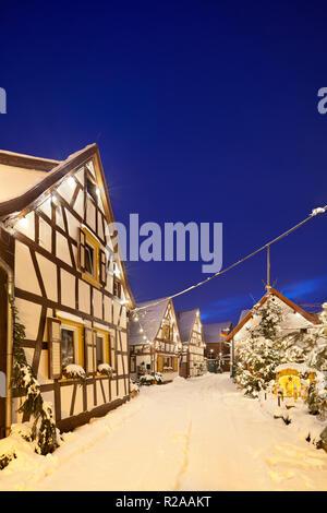 Un vecchio villaggio di strada con tipiche case a graticcio e decorazione di Natale di notte durante la nevicata a Lachen, Neustadt an der Weinstrasse, Germania. Foto Stock