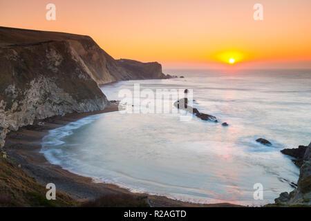 Lulworth, Dorset, Regno Unito. Il 18 novembre 2018. Il sole sorge sull uomo O'guerra bay su Jurassic Coast di Dorset nei pressi di Lulworth su una chiara fredda mattina. Credito Foto: Graham Hunt/Alamy Live News. Foto Stock