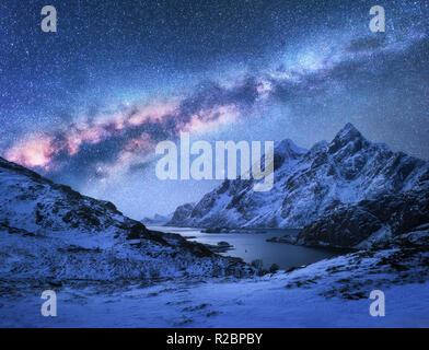Brillante Via Lattea su montagne coperte di neve e di Baia Mare in una notte d'inverno in Norvegia. Paesaggio spettacolare con rocce innevate, cielo stellato e colorati di ga Foto Stock