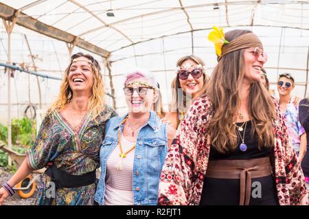 Stile hippy e vestiti e abiti per gruppo di femmine ribelle Free amici godendo e celebrare insieme in amicizia con i colori e lo stile di vita alternativo. immagine luminosa con senior e giovani donne insieme divertendosi a sorridere e ridere Foto Stock