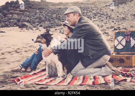 Coppia felice con un bel soggiorno cani in spiaggia facendo picnic a godersi la natura e la relazione. colori vintage e il filtro per i romantici e il concetto di viaggio immagine. diverso stile di vita da persone adulte Foto Stock
