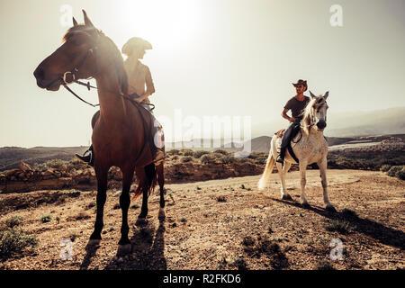 Coppia di cavalli e cowboy maschio e femmina ride free nella natura sulle montagne di Tenerife. Lo stile di vita e opere alternative o attività di svago di concetto per uomo e donna Foto Stock