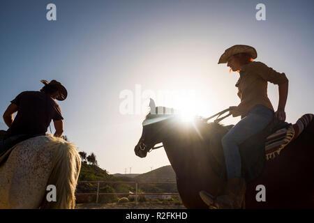 Paio di moderni cow-boy, l uomo e la donna ride due cavalli all'aperto con la sunflare e retroilluminazione. montagne e il mulino a vento in background. bella giovane in vacanza Foto Stock