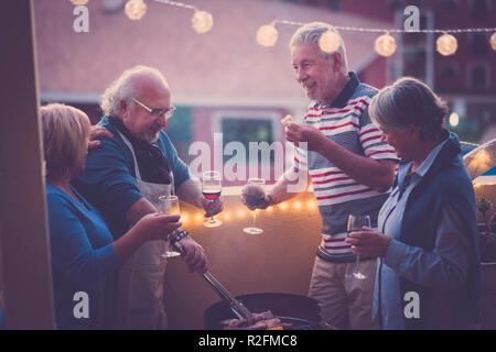 Grigliata bbq e qualche vino per festeggiare un evento. gruppo di persone adulte godetevi lo stile di vita all'aperto in terrazza con vista sulla città. mangiare mangiare e bere un bicchiere di vino Foto Stock