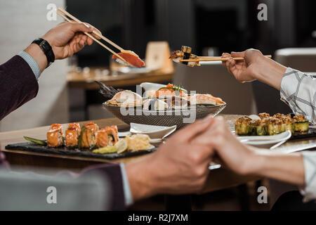 Vista parziale del giovane tenendo le mani mentre mangiando insieme rotoli di sushi al ristorante Foto Stock