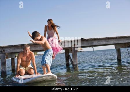 Ragazzo paddle imbarco con la sua metà adulto padre sul mare. Foto Stock