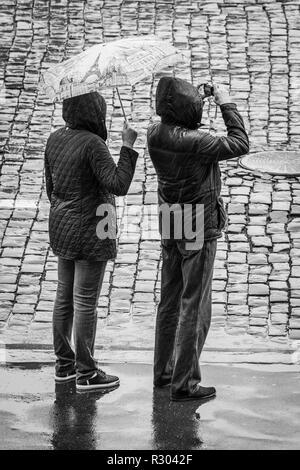 Turisti sotto la pioggia sulla Piazza Rossa di Mosca, Russia. Uomo e donna che indossa impermeabili, tenendo un ombrello mentre la fotografia. Foto Stock