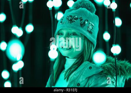 Kew Gardens, Londra, 21 Nov 2018. I bambini si divertono nella passerella ipnotiche di centinaia di nastri sospesi di luce.Tornando al Royal Botanical Gardens di Kew è Natale a Kew, un sentiero illuminato attraverso Kew dopo-paesaggio scuro, illuminata da oltre un milione di luci scintillanti e dotato di spettacolari installazioni luminose e sonore lungo il percorso, con tunnel di luce e, alla fine, la spettacolare Palm House Gran Finale con laser show. (Tutti i modelli di bambino sono stati forniti dalla sede e che il consenso è stato ottenuto) Credito: Imageplotter News e sport/Alamy Live News Foto Stock