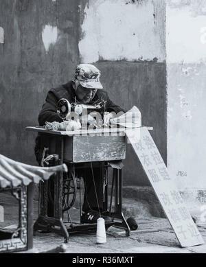Foto in bianco e nero di persone anziane uomo cinese guadagnarsi da vivere utilizzando una macchina per cucire per alterazioni di abbigliamento in una strada in Cina Dali. Foto Stock