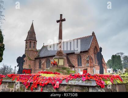Lavorato a maglia e ad uncinetto papaveri rossi sul display insieme al soldato permanente di sagome, al di fuori del Regno Unito sagrato, dal Memoriale di guerra. Armistizio centenario. Foto Stock