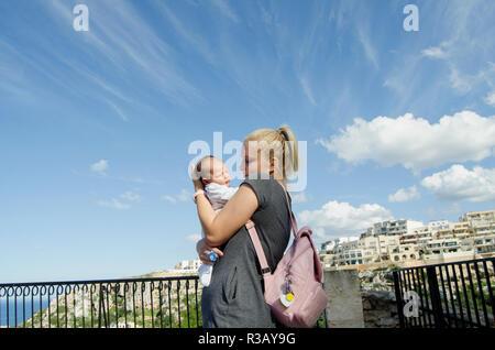 Giovane biondo mom tenendo un mese baby boy, cielo blu, giornata soleggiata Mellieha Malta Foto Stock