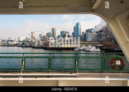 Stati Uniti d'America, WA, Seattle. Lungomare nel sole di mattina incorniciato dalla struttura del traghetto. Seattle grande ruota e lo Space Needle Foto Stock