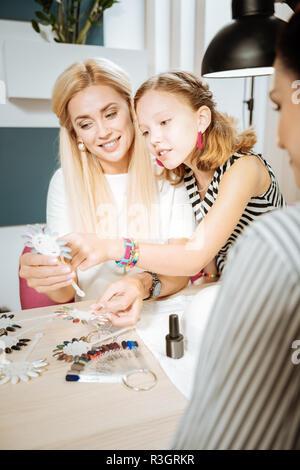 Figlia di indossare orecchini rosa aiutando la madre nella scelta di colore per unghie Foto Stock