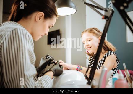 La madre lavora come artista per unghie manicure facendo per il suo simpatico figlia adolescente Foto Stock
