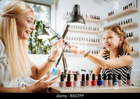 Figlia di utile raccomandare il colore dello smalto per unghie di sua madre Foto Stock