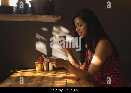 Donna che utilizza il cellulare mentre un caffè nella caffetteria
