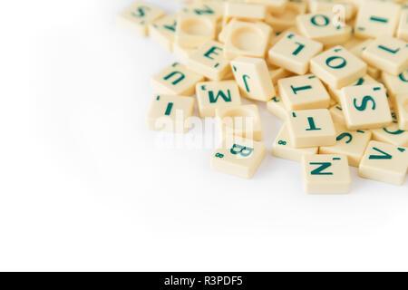 Pila di casuale gioco SCRABBLE lettera di piastrelle con valore di punteggio miscelati, isolati su sfondo bianco. Copia dello spazio. Foto Stock
