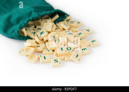 Random gioco SCRABBLE lettera di piastrelle con valore di punteggio proveniente dal loro verde borsa a cordoncino, isolato su sfondo bianco. Foto Stock